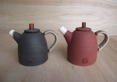 Stoneware medium sized teapots glazed on the inside the outside colour is the clay body. Copper lid top and fine hemp sail makers thread on the handle.